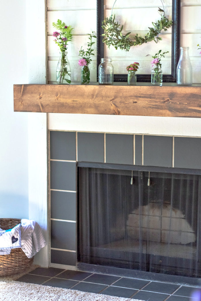 DIY fireplace mantel on a white fireplace with black tiles