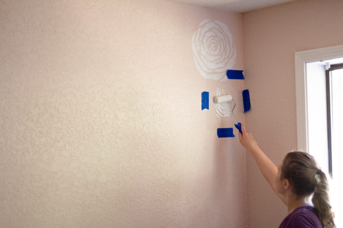 women painting white stenciled flowers onto a pink wall.