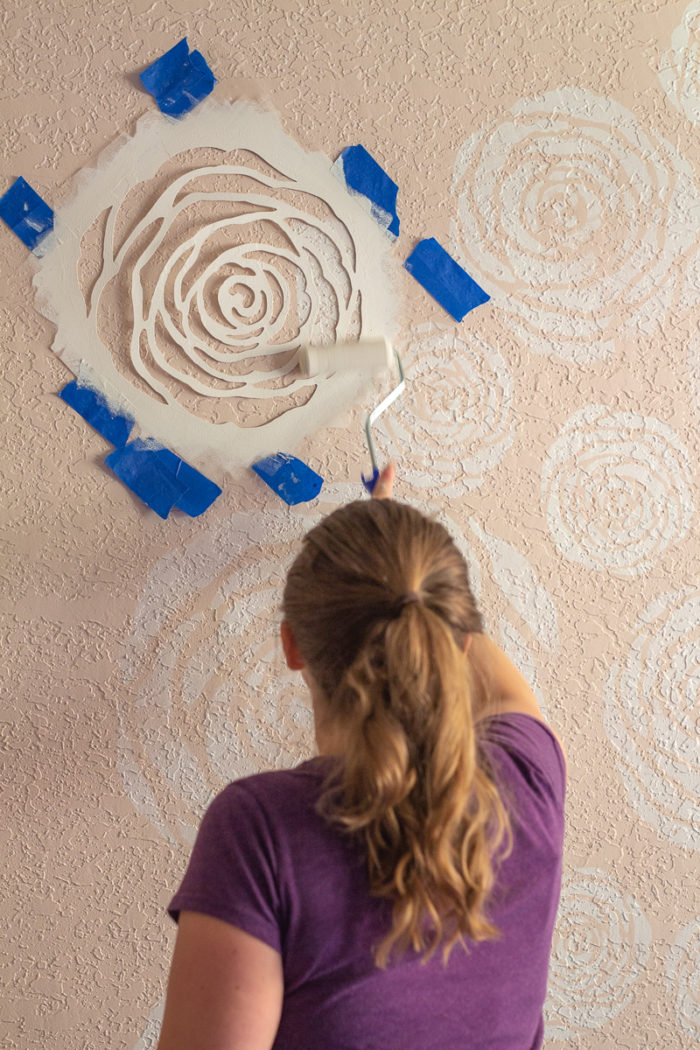 Women wearing purple shirt painting white stenciled flowers on wall
