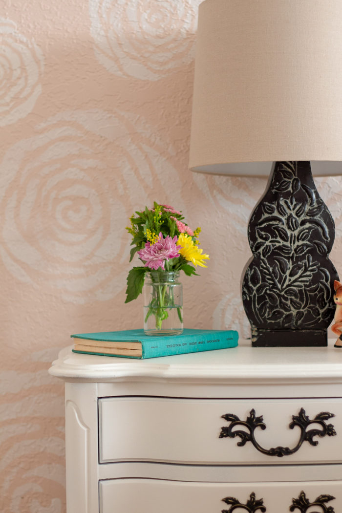 white painted antique nightstand topped with black lamp a turquoise book and mason jar filled with fresh flower in front of stenciled flower wall