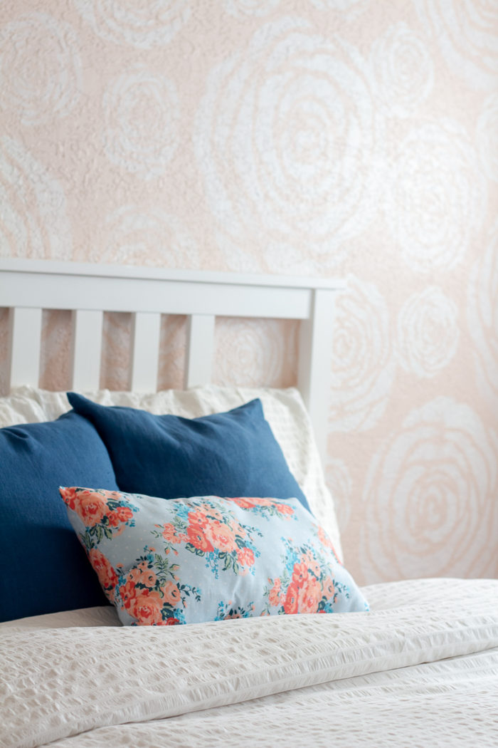DIY stenciled flowers on a wall with a bed in front with white linens and blue pillows