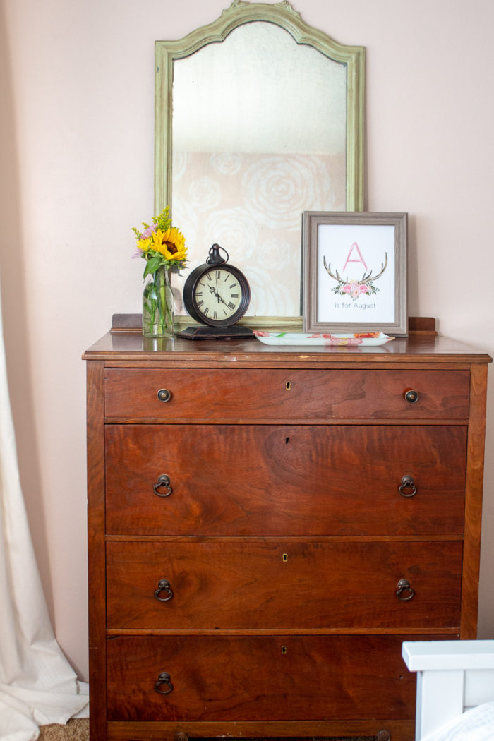 antique dresser topped with fresh flowers, clock, picture and antique green mirror.