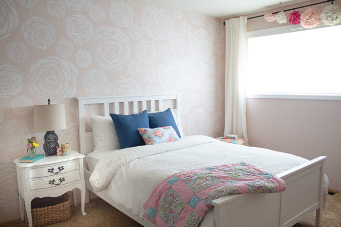 stenciled flowers on a wall with a white bed with white linens and blue pillow in front. An antique night stand to the left and a window with white linen curtains to the right