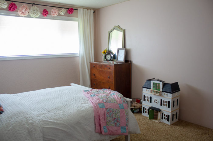 farmhouse style girls room with paper flower garland over window, antique dresser with antique green mirror. White magnolia dollhouse sits on the floor