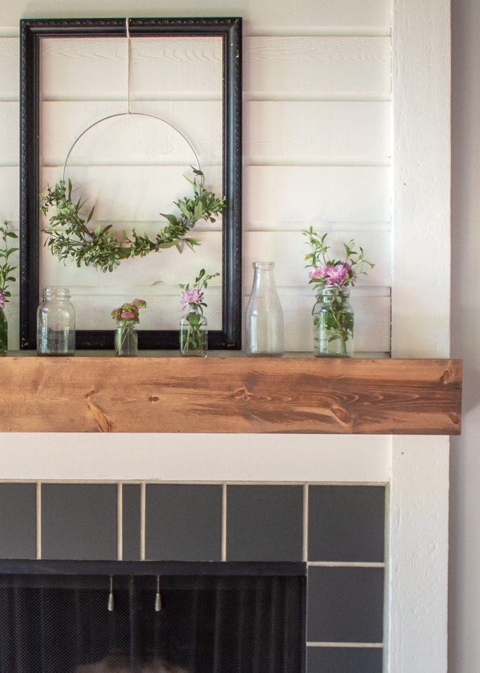 front half view of DIY fireplace mantel with stained wood and decorated with glass bottles, flowers, and a wreath- How to Build A Fireplace Mantel