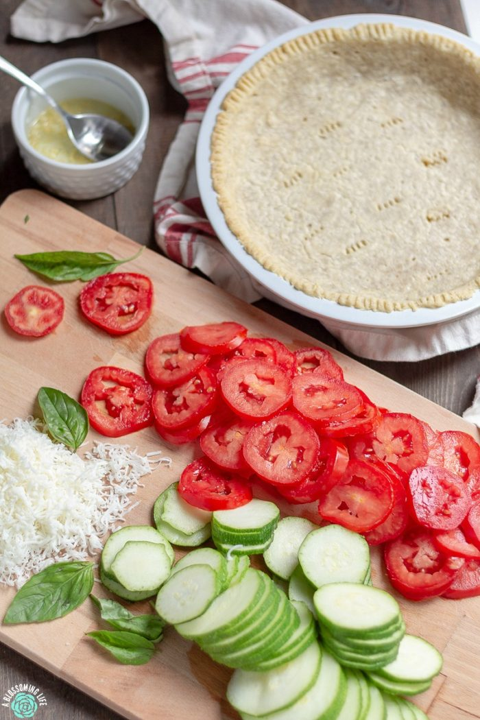 This tomato pie recipe has a perfectly flaky and buttery pie crust that is loaded with tomatoes and zucchini and a touch of garlic and cheese to make this delicious savory pie. Great recipe for when your garden is beaming with fresh zucchini and tomatoes.