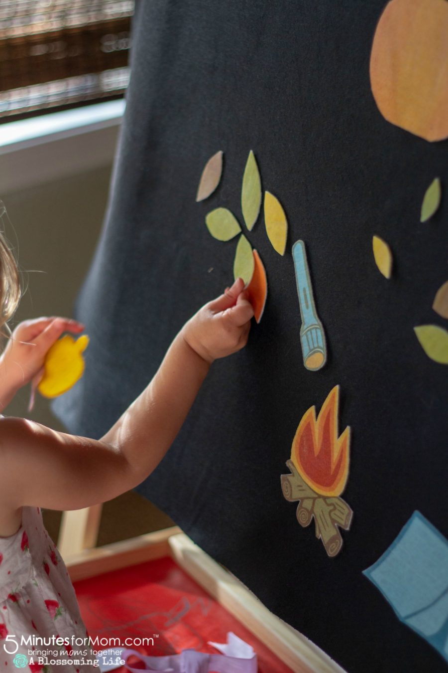 girl playing with a fall and camping themed felt board