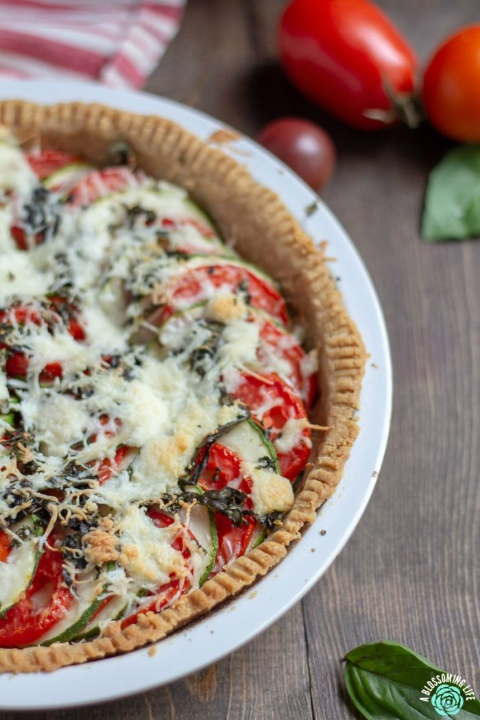 Tomato Pie - This tomato pie recipe has a perfectly flaky and buttery pie crust that is loaded with tomatoes and zucchini and a touch of garlic and cheese to make this delicious savory pie. Great recipe for when your garden is beaming with fresh zucchini and tomatoes.
