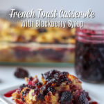 Slice of French Toast Casserole with Blackberries covered with blackberry syrup and a baking dish and jar of blackberry syrup in the back