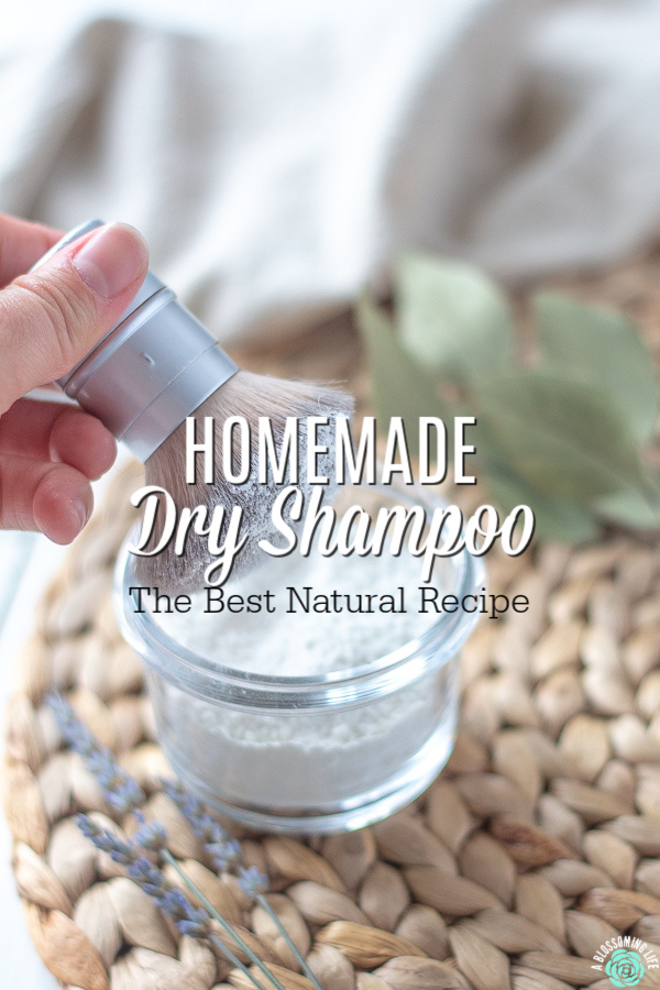 homemade dry shampoo in a glass container with a brush and lavender and eucalyptus around it