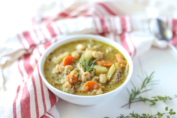 Bowl of chicken lentil soup- broth soup filled with carrots beans, potatoes, red split lentils and seasonings.