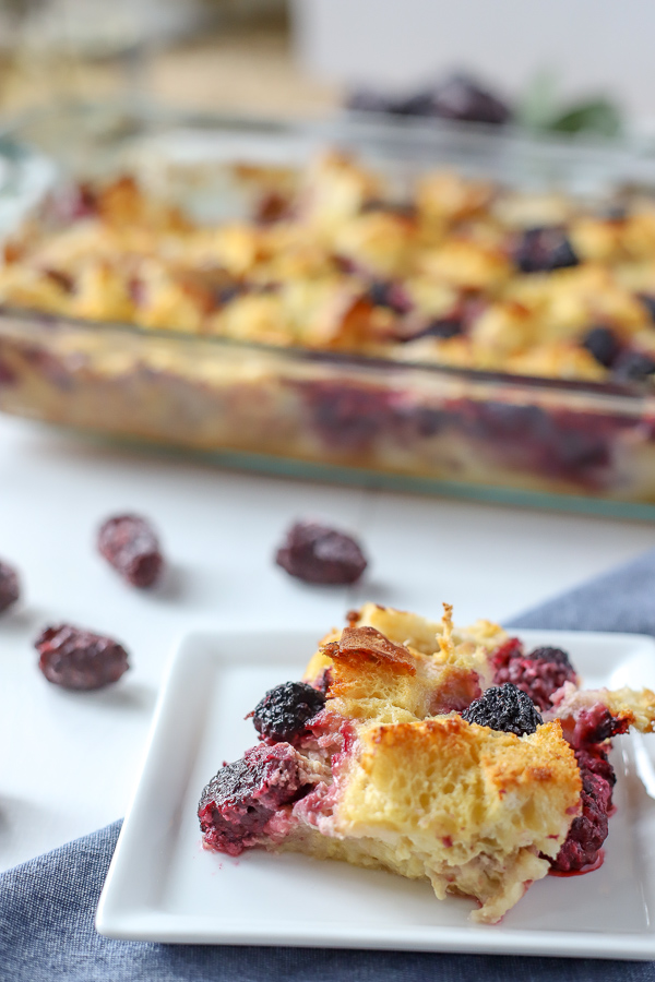 Slice of French Toast Casserole with Blackberries and a baking dish in the back