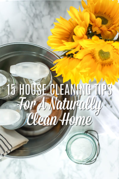 Metal bucket with cleaning products and a towel with Oxygen Boost in an antique jar to the right and sunflowers behind. - learn 15 house cleaning tips for a naturally clean home