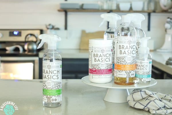 Branch Basics Products sitting on a cake stand on a kitchen counter with a towel next to it.