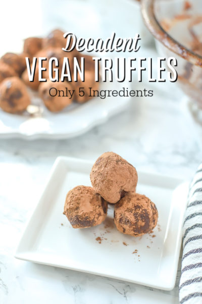 3 vegan truffles on a white square plate with a place of truffles behind it