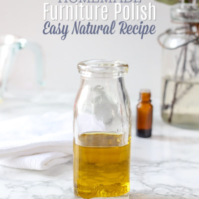 glass bottle of homemade furniture polish on a marble table with lavender flowers in front