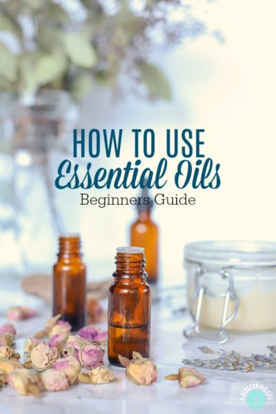 3 bottles of essential oils with rose buds, diy products, and eucalyptus behind it