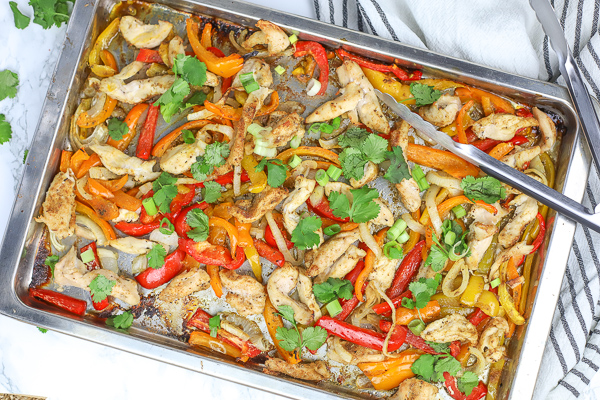sheet pan chicken fajitas with cilantro on a counter with a striped towel