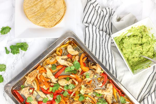 sheet pan chicken fajitas on a baking sheet with corn tortillas and guacamole on the side
