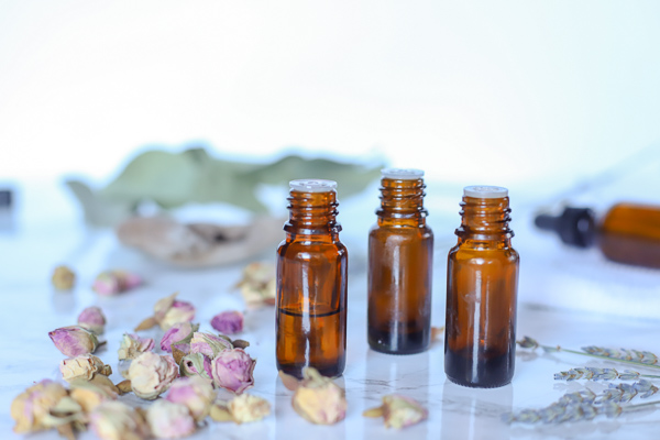3 bottles of essential oils with dried plants around