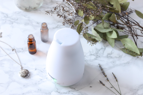 White essential oil diffuser with essential oils and eucalyptus behind it