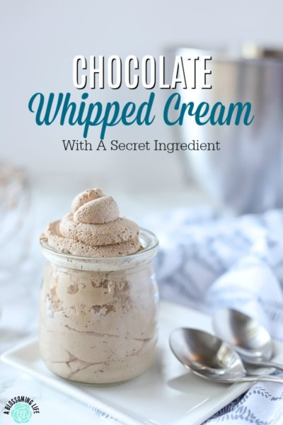 chocolate whipped cream in a glass dish on a white plate on a marble counter with two spoons
