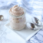 chocolate whipped cream in a glass container on a white plate with silver spoons