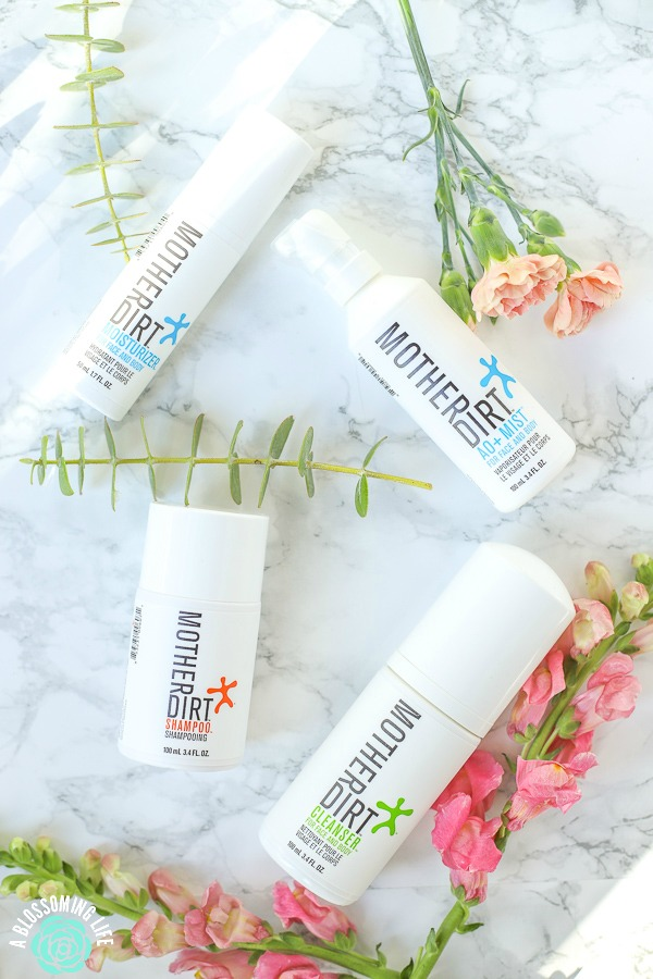 mother dirt probiotic skin care and biome-friendly products on a marble counter with flowers around them