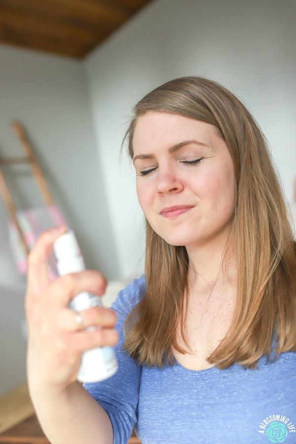 women in blue shirt spraying probiotics onto skin