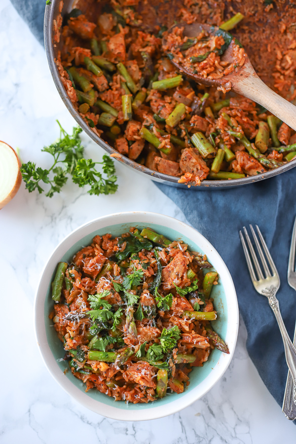 Italian Rice in a red sauce with vegetables in a dish with a skillet behind it
