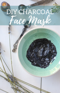 DIY charcoal face mask in a teal dish with dried lavender and measuring spoons around it