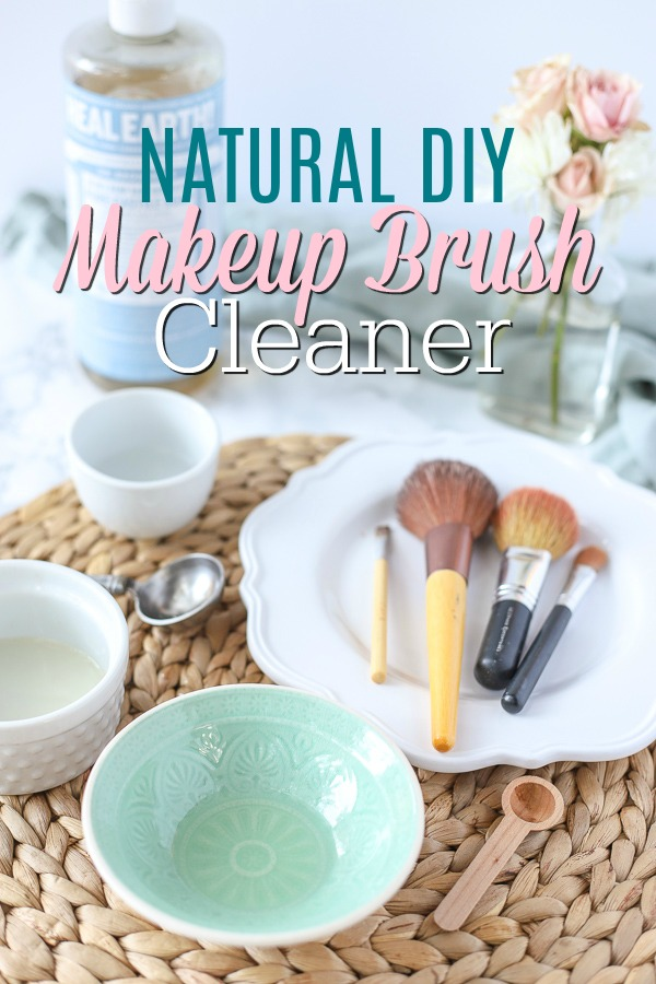Natural DIY makeup brush cleaner in a teal bowl on a ratan placemat with makeup brushes and ingredients behind it