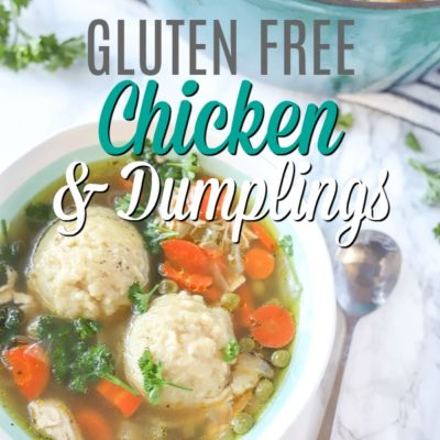 gluten free chicken in dumplings in a cream and teal bowl with a spoon to the right