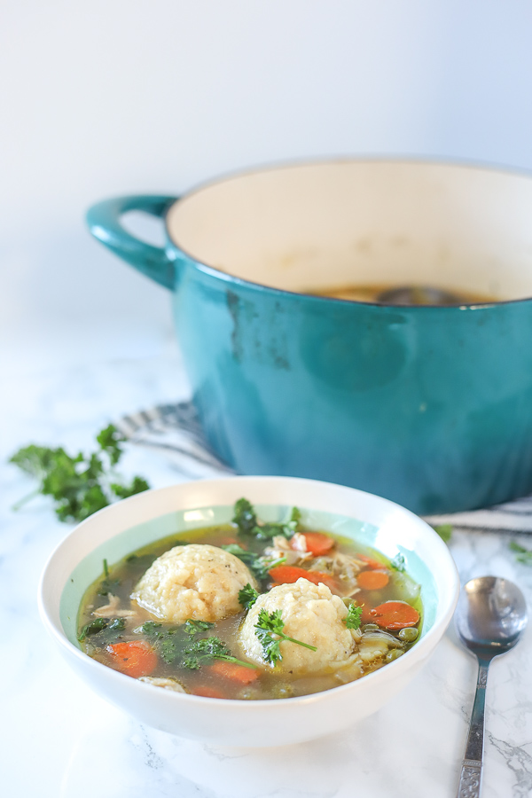 gluten free chicken and dumplings in a cream bowl with a large turquoise dutch oven behind it