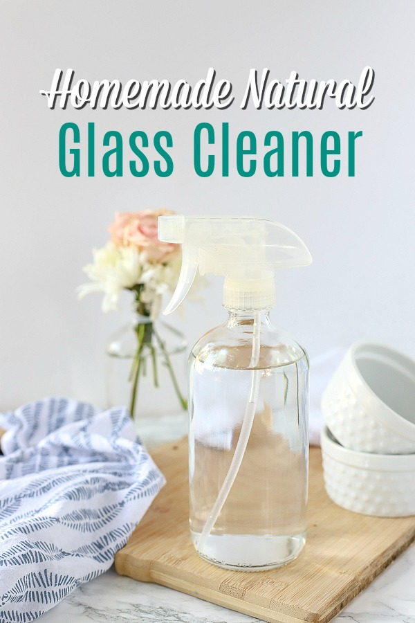 natural DIY glass cleaner in a glass bottle on a wood cutting board with a blue and white napkin and jars behind it