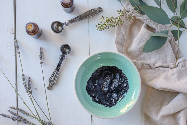 homemade activated charcoal mask in a teal bowl with measuring spoons and dried herbs around it.