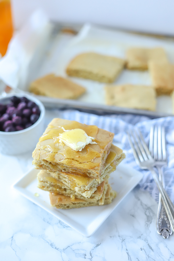 gluten free sheet pan pancakes stacked up four tall with butter and honey on a white dish and more pancakes behind it