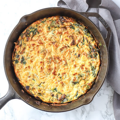 spinach frittata in a cast iron skillet with gray napkin