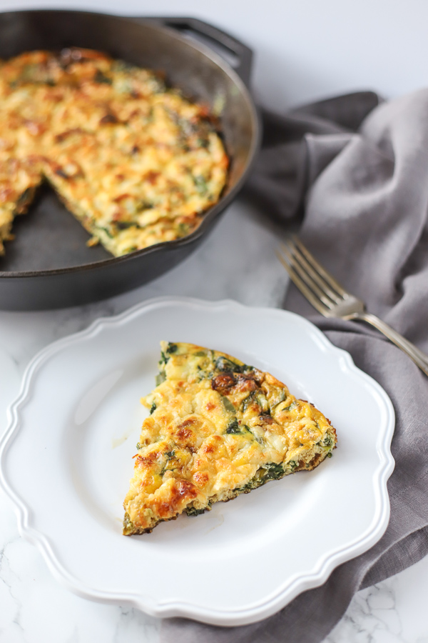 Spinach frittata on a white plate with a antique fork on a gray napkin
