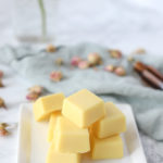 DIY lotion bar on a white place with essential oils and dried roses behind it