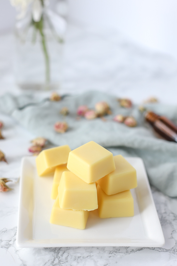 DIY lotion bar recipe on a white place with essential oils and dried roses behind it