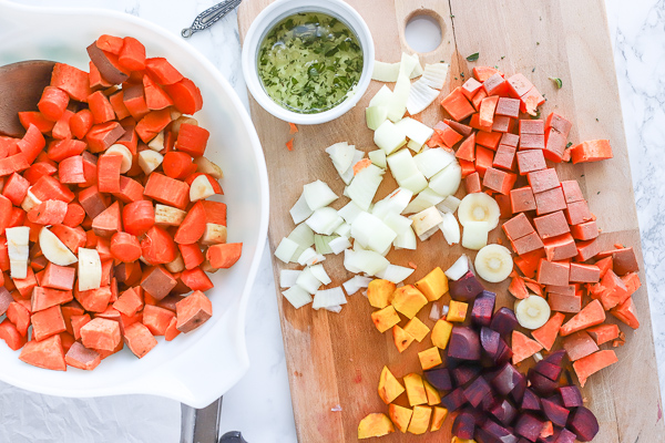 large bowl of chopped sweet potatoes next to a cutting board full of a variety of root vegetables for roasted root vegetables recipe