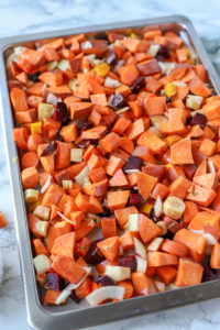 root vegetables on a parchment lined sheet pan getting ready for roasting