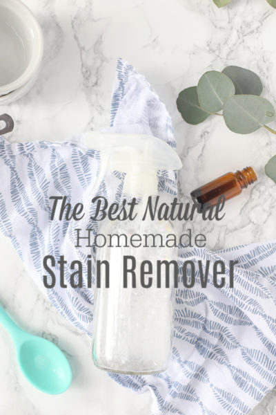 Natural homemade stain remover in a glass bottle on a blue and white napkin