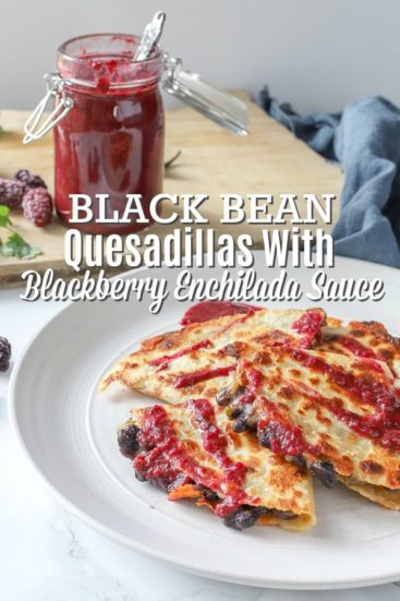 Black bean quesadillas topped with blackberry enchilada sauce on a stone plate with enchilada sauce in jar behind it.