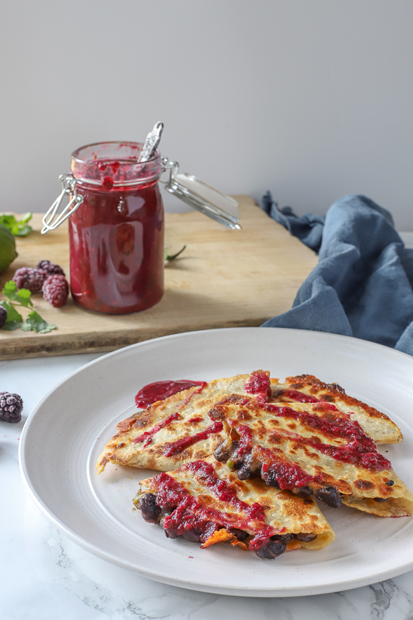 black bean quesadillas topped with blackberry enchilada sauce on a stone plate