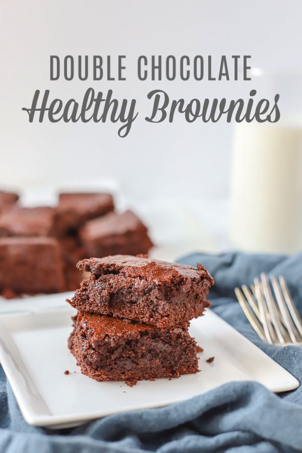 two double chocolate healthy brownies stacked on a white plate on top a blue napkin with a glass of milk and more brownies behind it