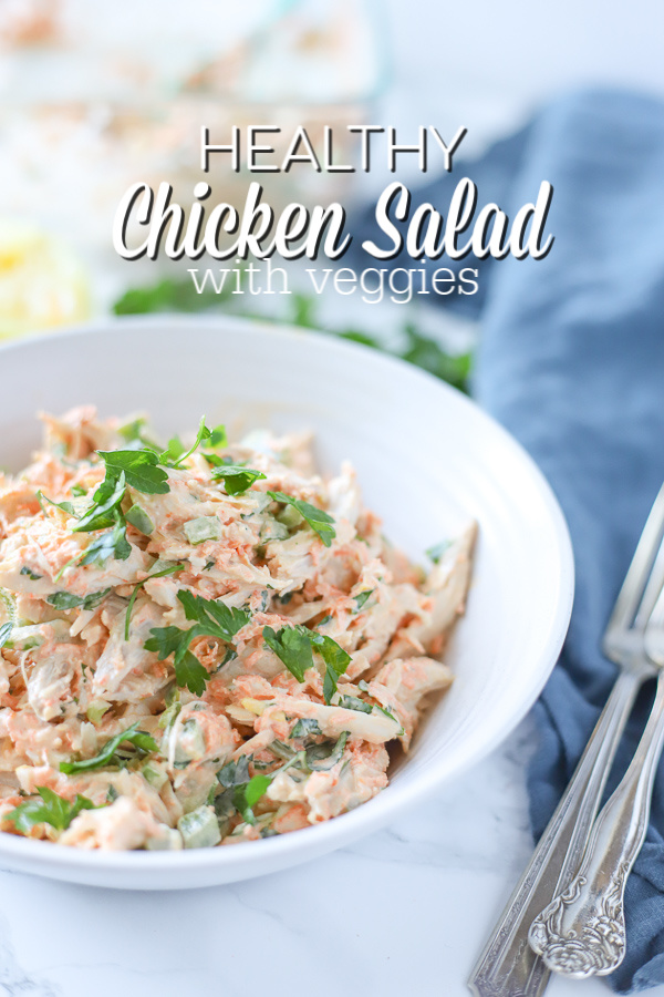 healthy chicken salad in a white bowl on top a blue napkin with antique forks to the right