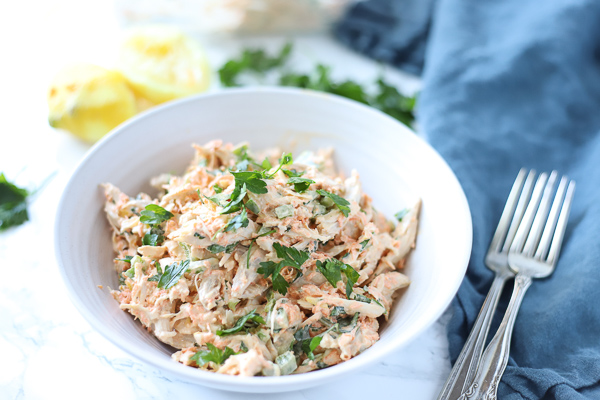 healthy chicken salad in a white bowl with lemons behind it