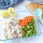 chicken, peppers, and carrots in glass bowl to make healthy chicken salad